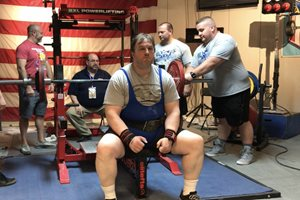 Daniel Cotter, now of Howard & Howard, prepares for a bench press during the American Powerlifting Federation-Illinois' Chicago Summer Bash in Lombard July 26. Cotter used the event to raise funds for Lawyers Lend-A-Hand to Youth's tutoring program in Englewood. Gathering pledges based on the weight he would lift in competition, he raised $12,000 by bench-pressing 319.7 pounds — also enough to win first place in his division.